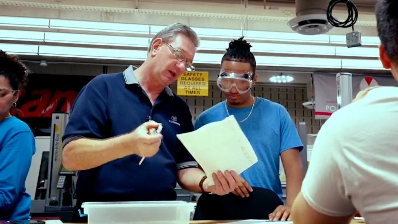 An instructor holding a sheet of paper talks to a student wearing safety glasses.